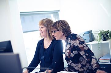 To kvinner som ser på en skjerm sammen