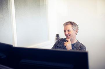 Smilende mann foran skjerm