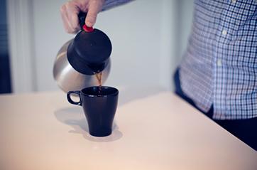 Arm som heller kaffe i en kopp.