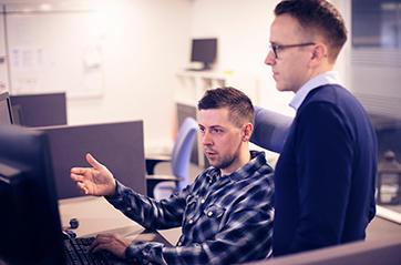 To menn som ser på en skjerm sammen.