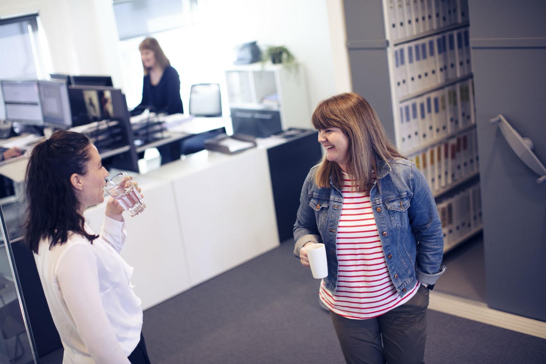 To kvinner som snakker og ler sammen i et kontorlandskap