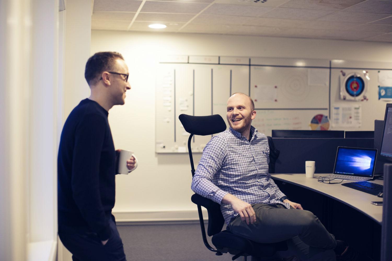 To menn som snakker og ler sammen i et godt arbeidsmiljø