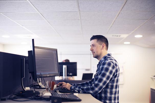 Systemutvikler som jobber foran skjerm